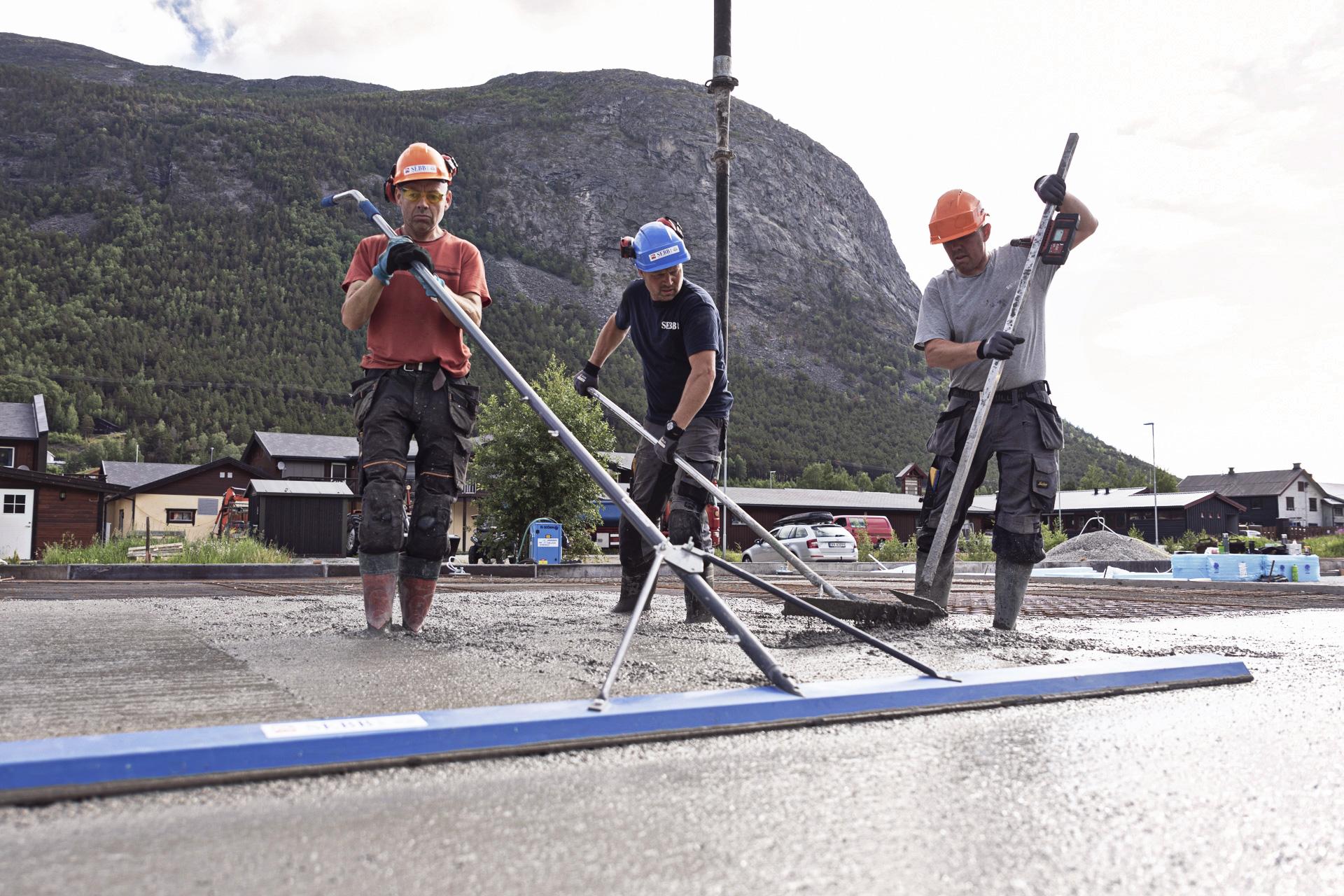 Tre personer som støper betonggulv